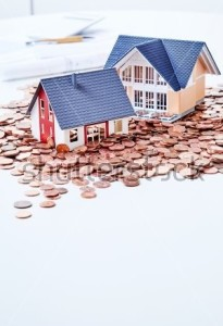 stock-photo-miniatures-of-two-houses-standing-among-coins-683983537